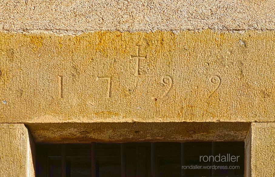 Llinda de porta amb una creu i la data 1799. Amulets per espantar bruixes. Vall de Llémena. Gironès