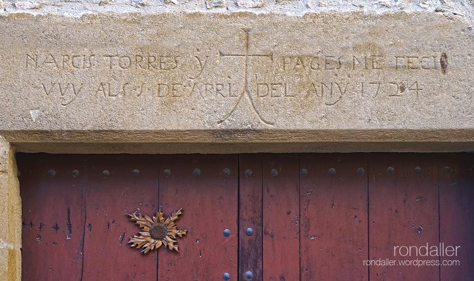 Llinda amb una inscripció de 1724, una creu i una carlina clavada a la porta. Símbols protectors a Madremanya. Gironès